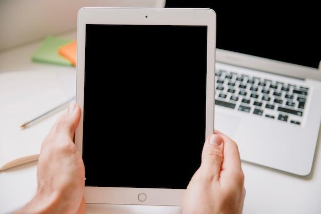 Technologie- und schreibtischkonzept mit den händen, die tablette halten