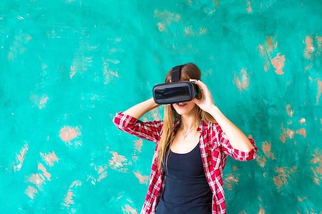 Technologie, virtuelle realität, unterhaltung und menschenkonzept. glückliche junge frau mit virtual-reality-headset oder 3d-brille und kopfhörer auf grauem hintergrund