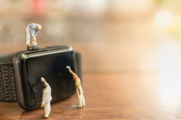 Technologie, zeitkonzept. schließen sie oben von gruppe von arbeiter und maler miniaturfigur menschen reinigen und malen auf uhr auf holztisch und kopierraum.