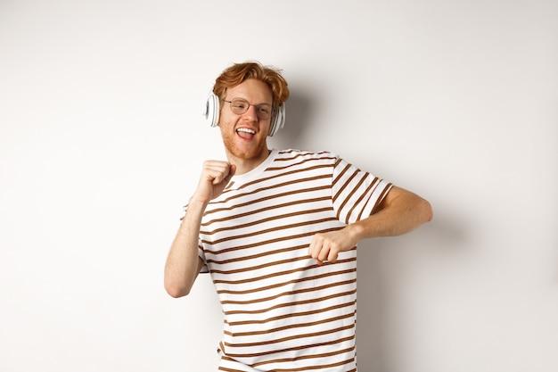 Technologiekonzept. glücklicher rothaariger mann, der musik in kopfhörern hört und fröhlich tanzt und im t-shirt vor weißem hintergrund steht.