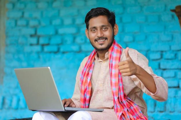 Technologiekonzept: indischer bauer, der laptop benutzt und zu hause thumps zeigt