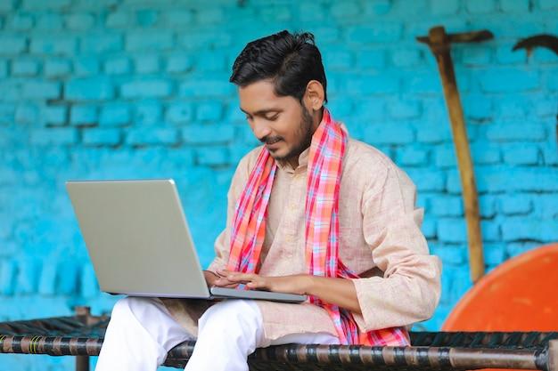 Technologiekonzept: indischer bauer mit laptop zu hause