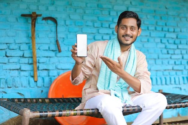 Technologiekonzept: junger indischer bauer, der smartphone in seinem haus zeigt
