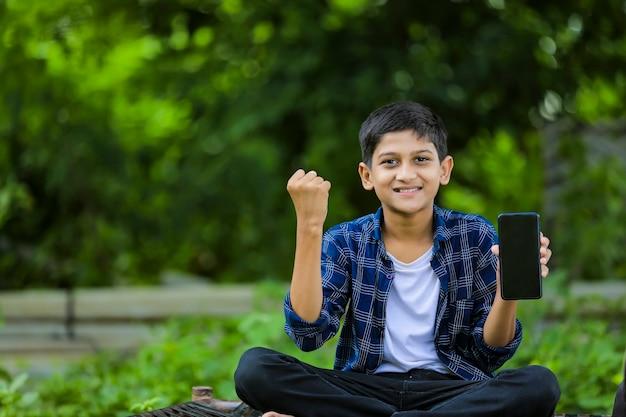 Technologiekonzept: netter indischer kleiner schuljunge, der tasche hält und smartphone zeigt