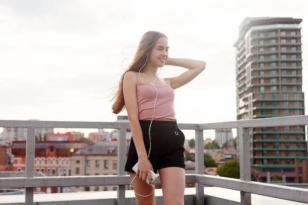 Technologien, emotionen, menschen, musik, schönheit, mode und lifestyle-konzept - junge frau mit kopfhörern, die an ihrem handy baumeln, während sie in einer städtischen straße geht, blick aus der höhe