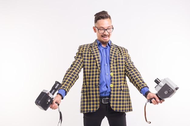 Technologien, fotografie und menschenkonzept - porträt eines lustigen jungen brünetten mannes, der selfie mit zwei kameras auf weißem hintergrund macht.