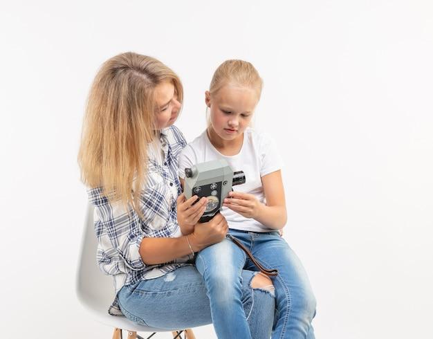 Technologien, fotografieren und familienkonzept - mutter und tochter mit retro-kamera auf weißem hintergrund.