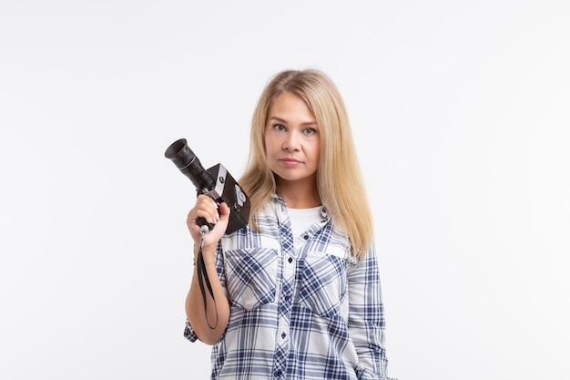 Technologien, fotografieren und menschen-konzept - blonde junge frau mit retro-kamera lächelnd auf weißem hintergrund.