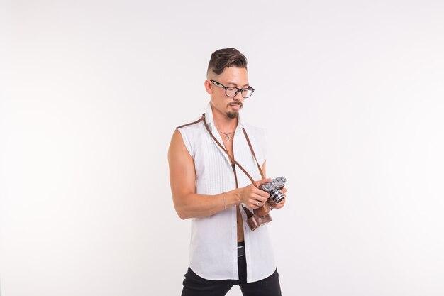 Technologien, fotografieren und menschenkonzept - hübscher junger mann mit retro-kamera auf weißem hintergrund.