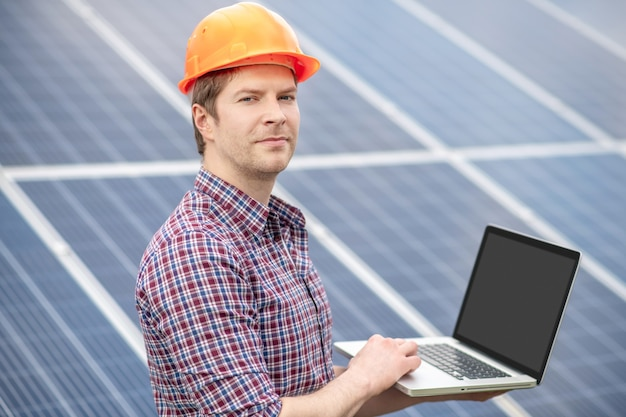Technologien. junger erwachsener erfahrener mann in schutzhelm, der mit laptop arbeitet, der im freien in der nähe von solarbatterie steht