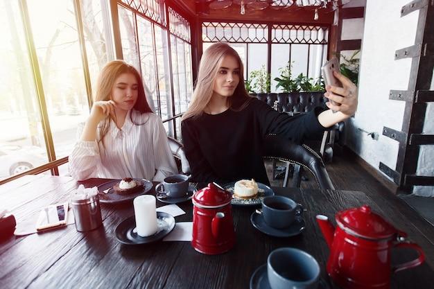 Technologien, lifestyle, essen, menschen, teenager und kaffeekonzept - zwei junge frauen machen selfie mit smartphone im stadtzentrum. glückskonzept über mensch und technik