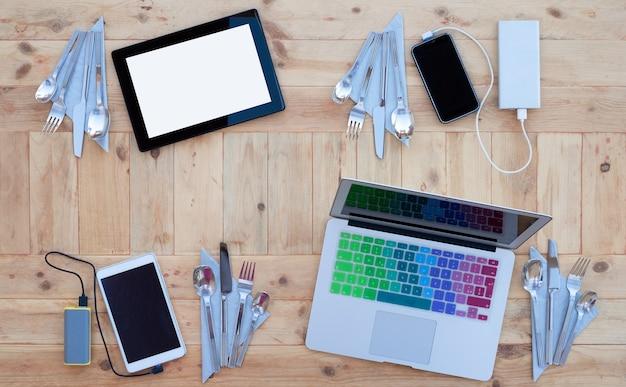 Technologischer tisch. vier plätze für updates und innovationen in den sozialen medien gebucht. guten appetit. holzhintergrund