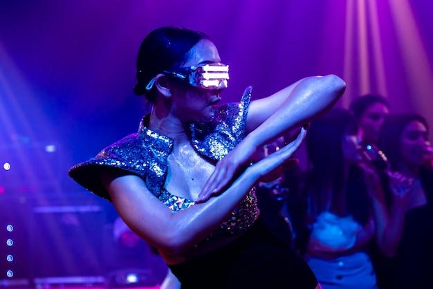Technotänzer im nachtclub, der im rhythmus der musik von dj tanzt