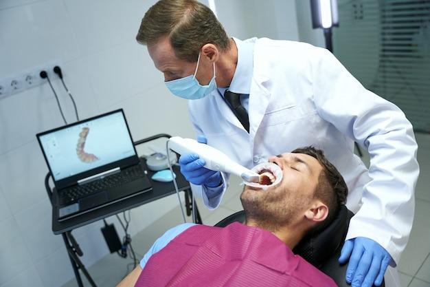 Techsmart-arzt inspiziert die zähne des patienten mit einem speziellen gerät