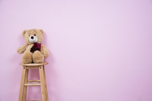 Teddy bear auf einem holzstuhl mit rosa wänden