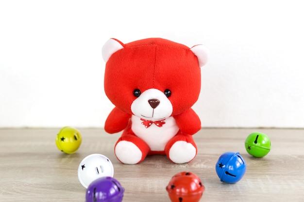 Teddy bear-spielzeug, das allein auf holz im vorderen weißen hintergrund mit bunter glocke sitzt