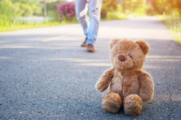 Teddybär allein sitzt auf der straße, trauriges konzept