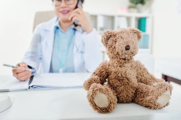 Teddybär auf dem schreibtisch des kinderarztes