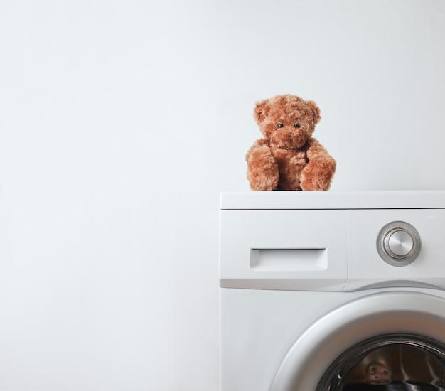 Teddybär auf einer waschmaschine gegen eine weiße oberfläche