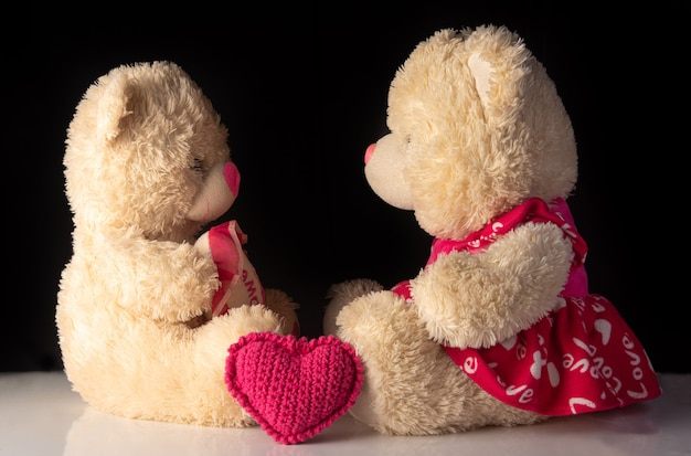 Teddybär auf weißer oberfläche, auf schwarzem hintergrund, selektiver fokus.