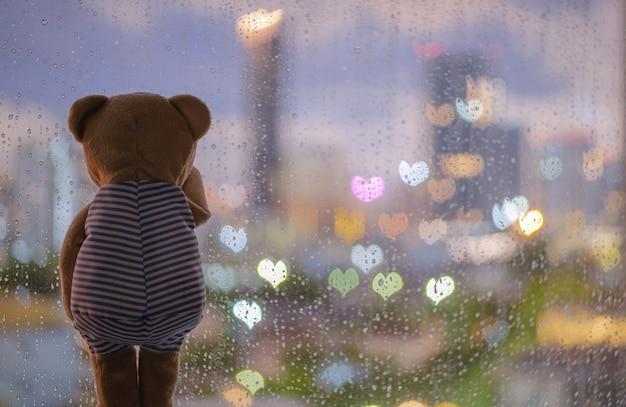 Teddybär, der allein am fenster weint, wenn er mit bunten liebesform-bokeh-lichtern regnet.