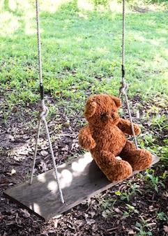 Teddybär, der auf schwingen über rasen sitzt. alleine fühlen. lieblingspuppe der kindheit.