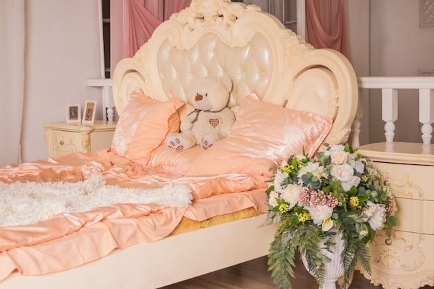 Teddybär, der auf weißem bett im gemütlichen und hellen schlafzimmer sitzt.