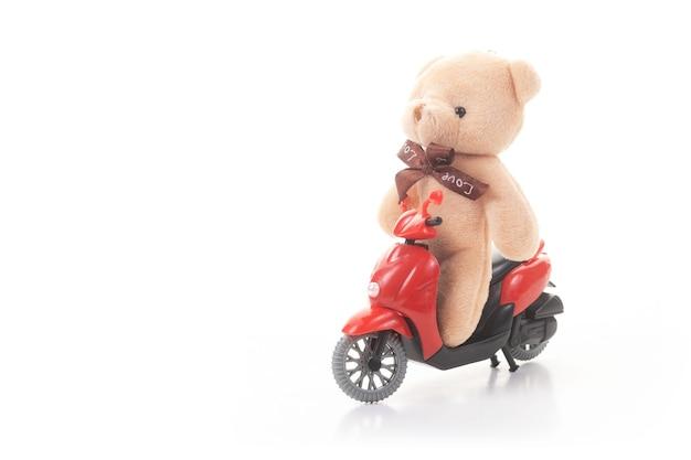 Teddybär, der ein motorrad auf weißem hintergrund reitet. konzept des online-lebensmittelliefergeschäfts.