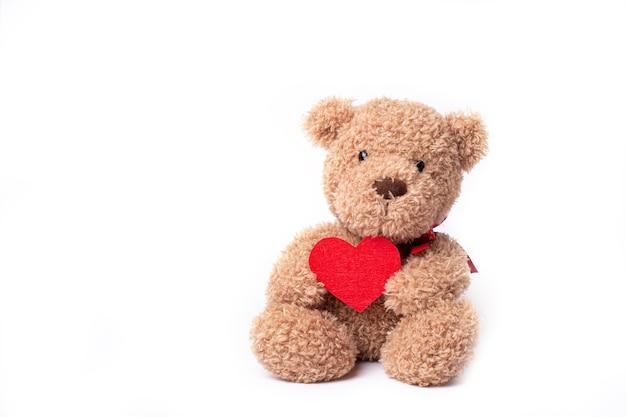Teddybär, der herz lokalisiert auf weiß hält