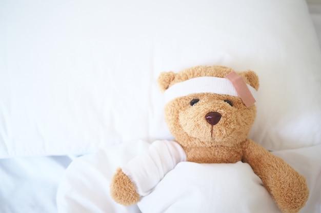Teddybär, der krank im bett liegt mit einem stirnband und einem stoff bedeckt