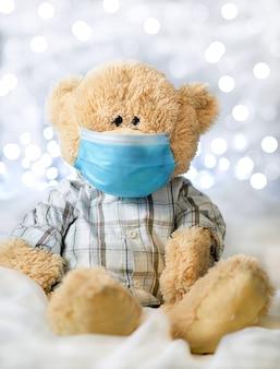 Teddybär im hemd und in der blauen medizinischen maske