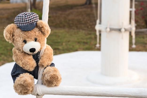 Teddybär im spielplatz hängen