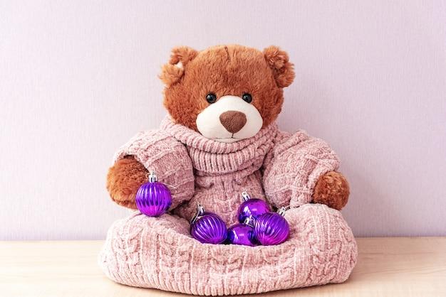 Teddybär im strickpullover mit weihnachtsschmuck
