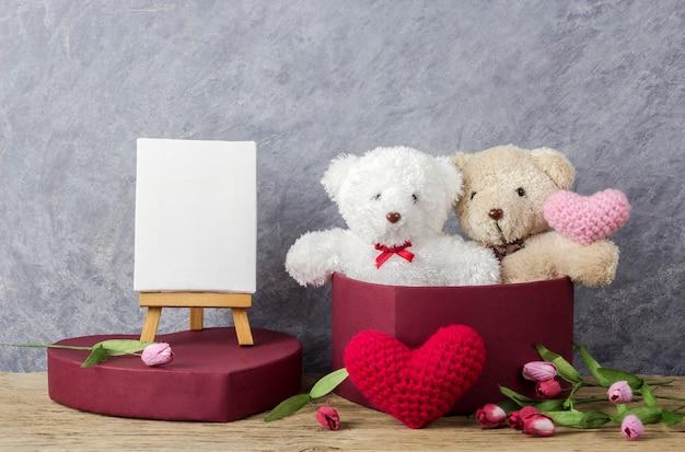 Teddybär in der roten herzgeschenkbox auf hölzerner tabelle und leerem segeltuchrahmen auf gestellmalerei