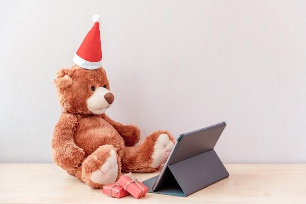 Teddybär in der weihnachtsmütze mit winzigen geschenken, die an der tafel sitzen