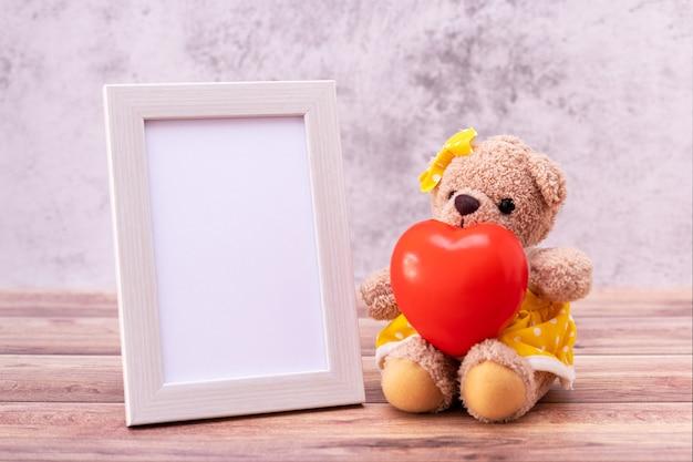 Teddybär mit bilderrahmen auf tisch aus holz. valentinstag feier