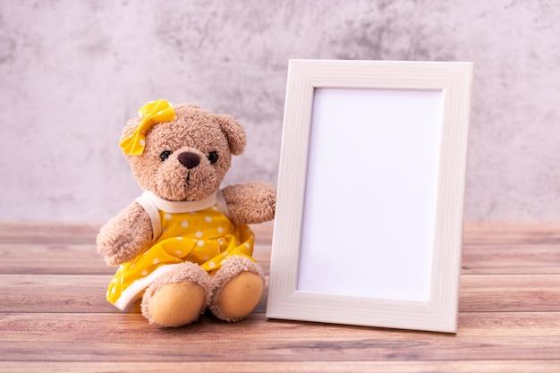 Teddybär mit bilderrahmen auf tisch aus holz.