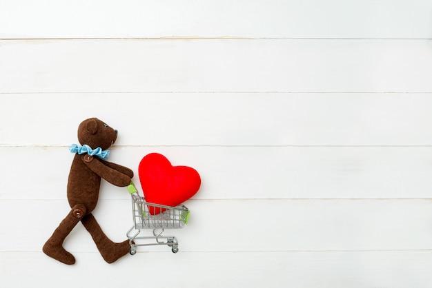 Teddybär mit einem herzen in den händen auf einem weißen hintergrund