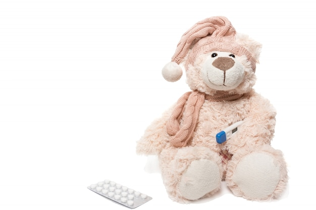Teddybär mit einem thermometer und pillen
