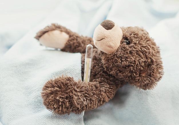 Teddybär mit einem thermometer