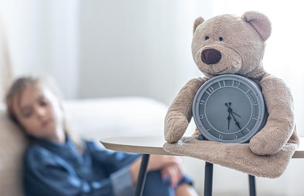 Teddybär mit einem wecker auf einem unscharfen hintergrund des zimmers eines kleinen mädchens.