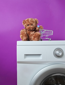 Teddybär mit einkaufswagen auf einer waschmaschine