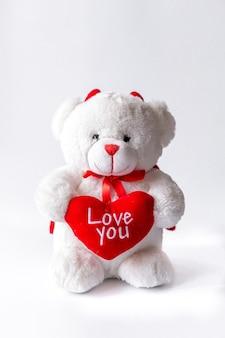 Teddybär mit herz in der hand auf weißem hintergrund