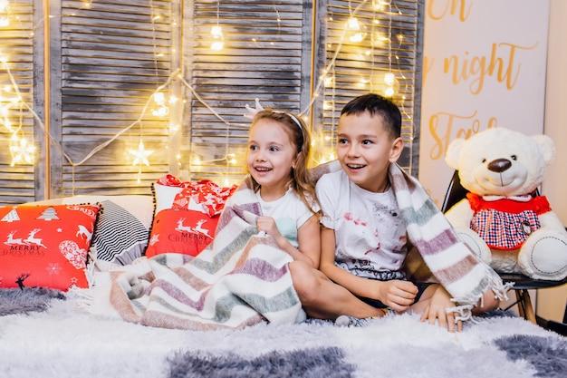 Teddybär mit kindern in einem plaid in einem modernen raum mit den kissen und den weihnachtsgirlanden des neuen jahres