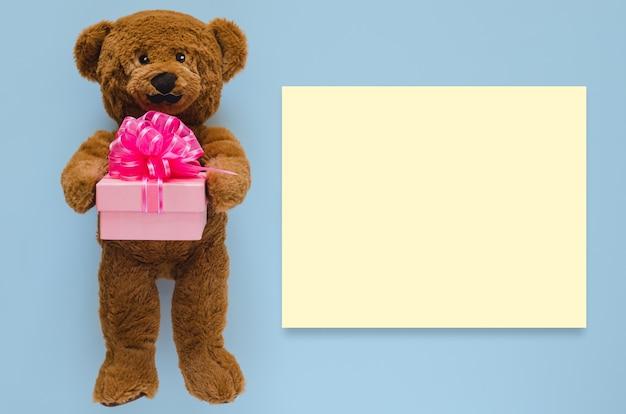 Teddybär mit schnurrbart, der geschenkbox mit leerem gelbem raum für text hält