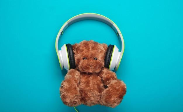 Teddybär mit stereokopfhörern auf blauer oberfläche