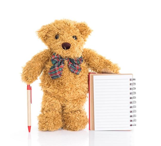 Teddybär mit stift und leerem notizbuch