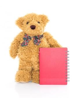Teddybär mit stift und leerem rotem notizbuch