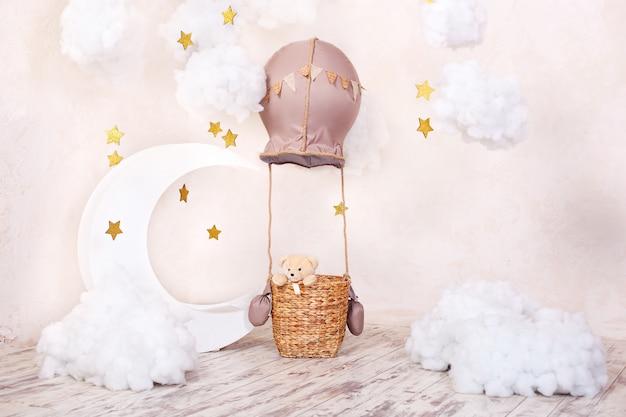 Teddybär reisender und pilot. kindheitsträume. stilvolles vintage kinderzimmer mit aerostat, luftballons und textilwolken. kinderstandort für ein fotoshooting: aerostat, ballon und wolken.