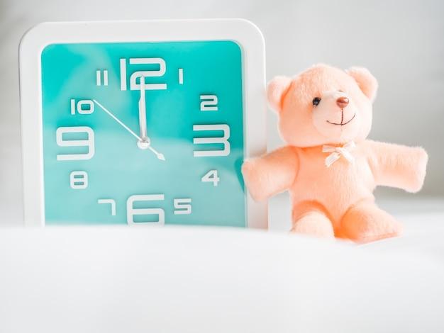 Teddybär spielzeug und uhr im schlafzimmer.